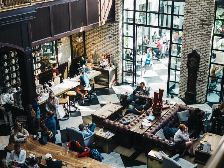 View from a balcony down into a busy café where most people are looking at their phones