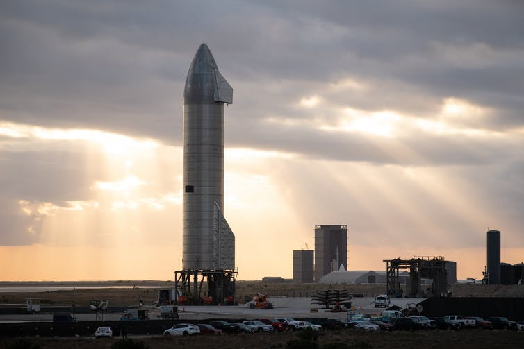 A large silvery rocket standing upright on a launchpad.