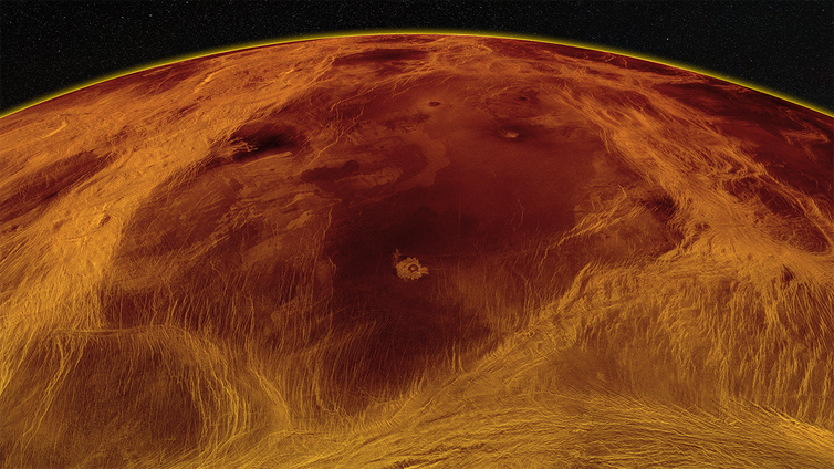 A red–hued image of the surface of Venus showing a large darker piece of the surface surrounded by lighter colors against the backdrop of space.