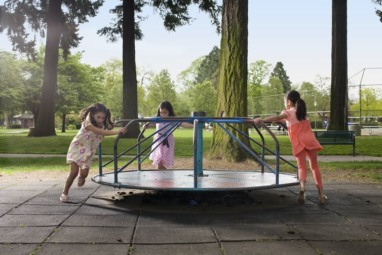 Three young girls playing on a playground carousel
