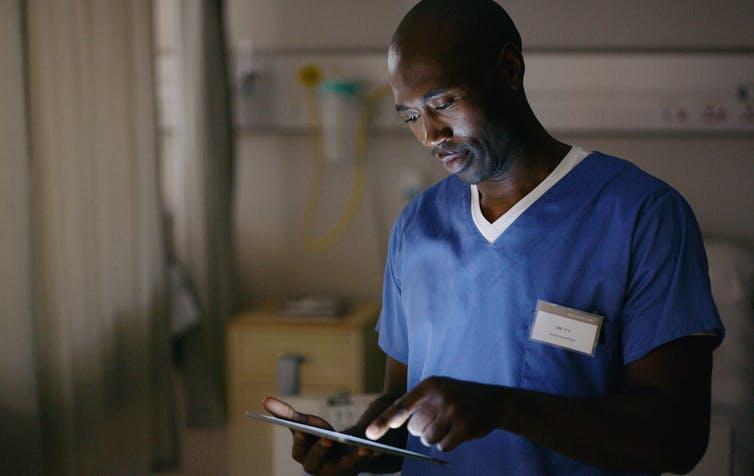 doctor in scrubs using tablet